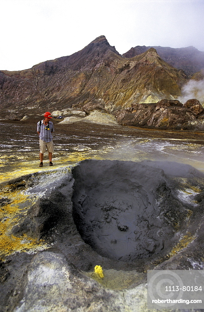 Tourist looking at boiling hot mud on White Island, North Island, New Zealand