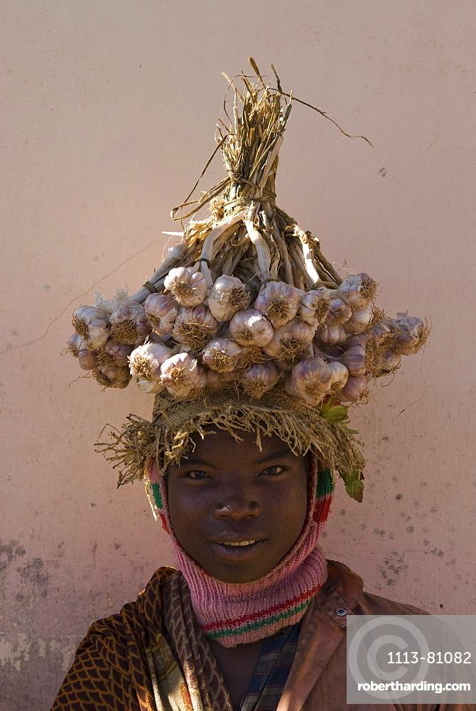 Local man carrying garlic on his head, Madagascar, Africa