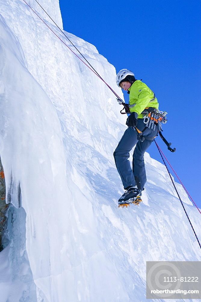 A jung man, an ice climber abseiling on the frozen waterfall, Corn Diavolezza near Pontresina, Grisons, Switzerland, MR