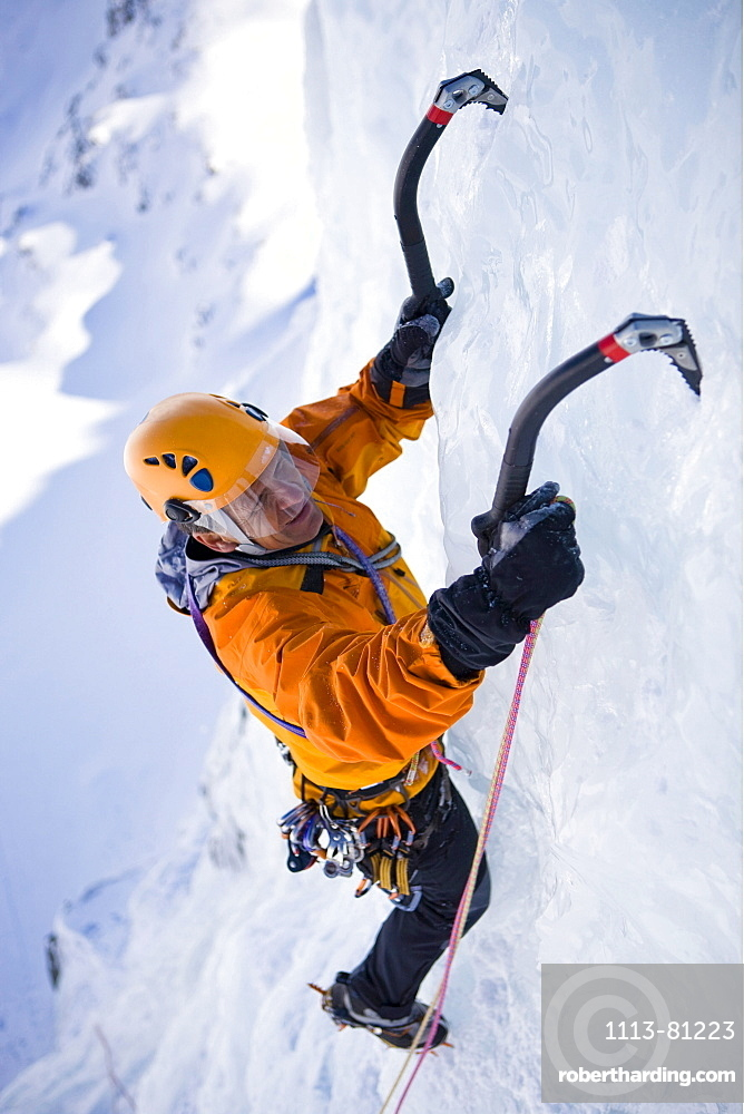 A man ice climbing on on a frozen waterfall, Corn Diavolezza near Pontresina, Grisons, Switzerland