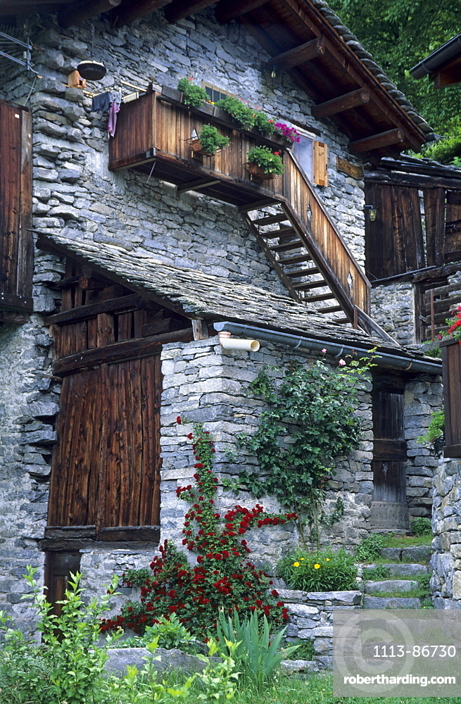 farmhouse with flower decoration and roses, Savogno, Valchiavenna, Bergell, Italy