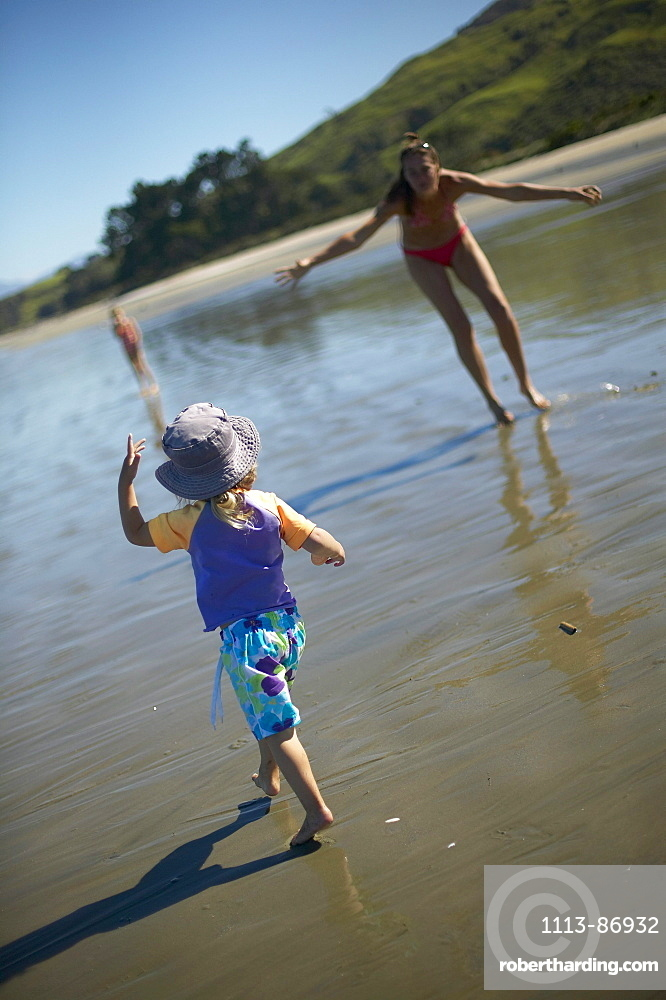 Mother and daughter playing at Pakawau beach, Golden Bay, northern coast of South Island, New Zealand