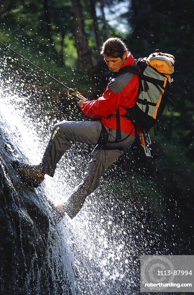 Man climbing, descending down a waterfall. Lake Sylvenstein, Upper Bavaria, Bavaria, Germany