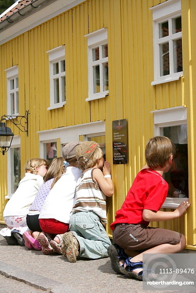 Children watching a Pippi Longstocking scene in a miniature house, Astrid Lindgren's World, Vimmerby, Smaland, Sweden