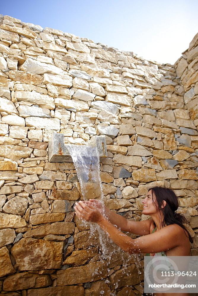 Woman in the outdoor shower with natural stone wall, Hotel Areias do Seixo, Povoa de Penafirme, A-dos-Cunhados, Costa de Prata, Portugal