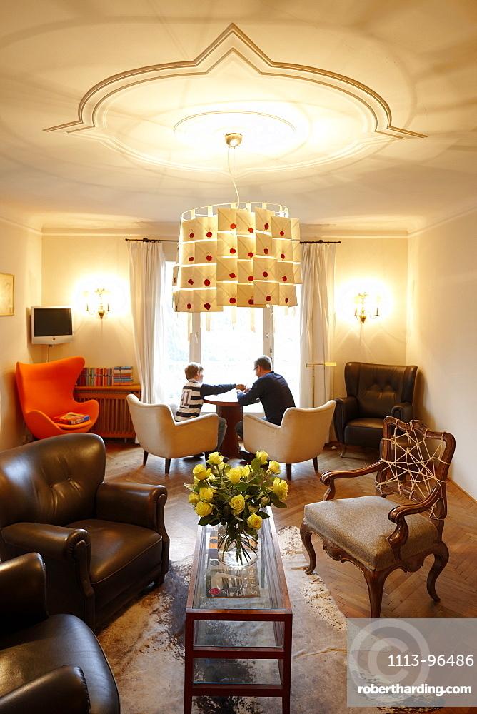 Father with son in the lounge of Hotel Haus Hirt, Bad Gastein, St. Johann im Pongau, Salzburg, Austria