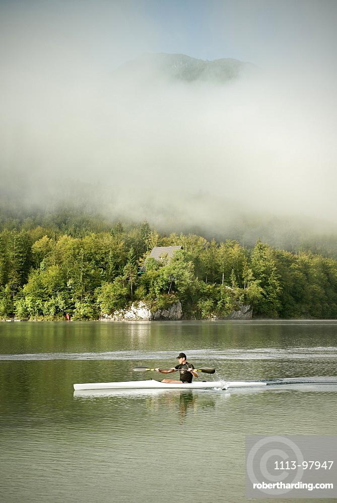 Kayak oarsman at Lake Bohinj, mist, Triglav National Park, Julian Alps, Gorenjska, Slovenia