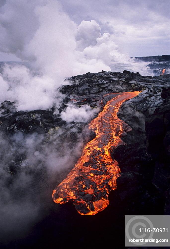 Hawaii, Big Island, Hawaii Volcanoes National Park, Molten lava flow, Steam clouds in distance.