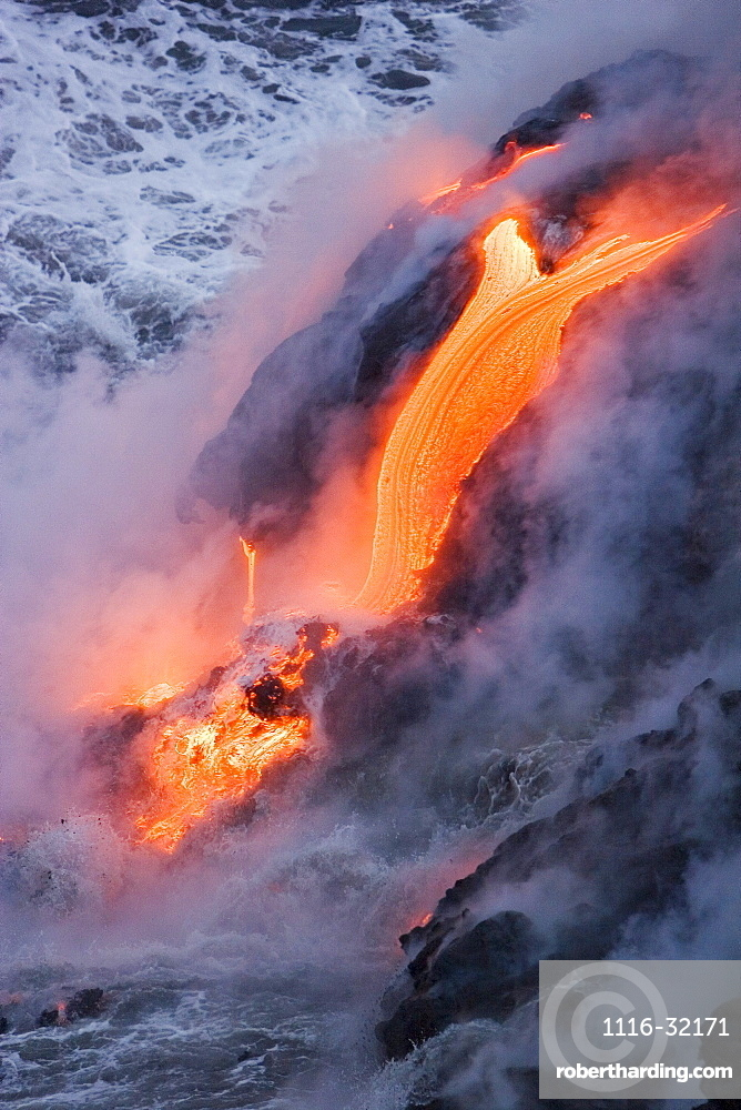 Hawaii, Big Island, near Kalapana, Pahoehoe lava flowing from Kilauea into frothy Pacific Ocean, Steam rising.