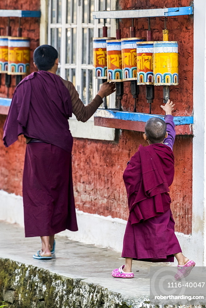 Young Buddhist monks walk by and touch the prayer wheels at Rinchenpong Monastery, Sikkim, India