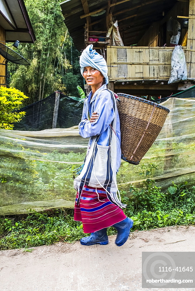 Young woman from the Karen tribe wearing traditional garments in a village, Thailand