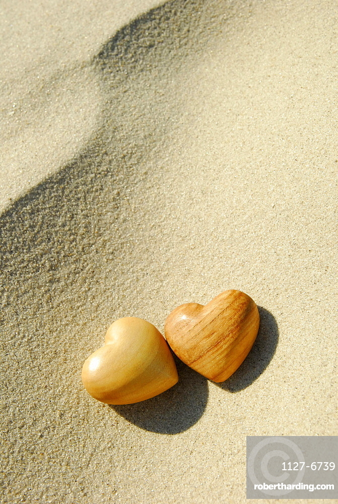 Wooden hearts on sand