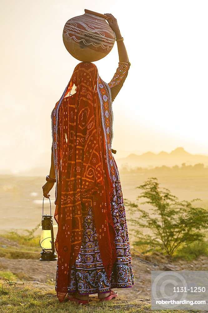 Ahir Woman in traditional colorful cloth carrying water in a clay jug on her head, Great Rann of Kutch Desert, Gujarat, India, Asia