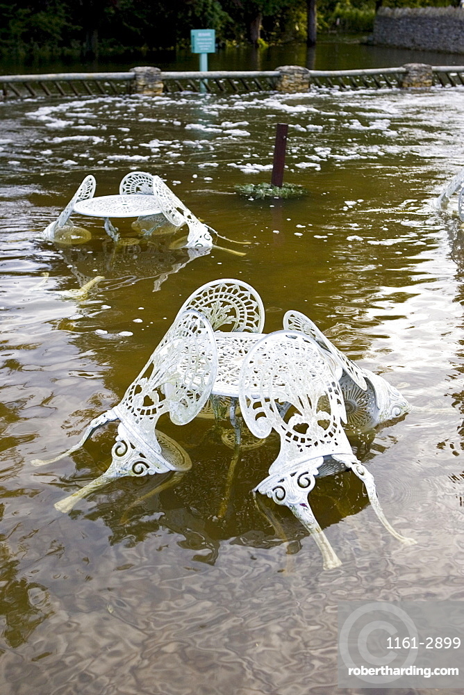 Outdoor tables and chairs of The Swan Hotel submerged in flood water, Minster Lovell, Oxfordshire, United Kingdom