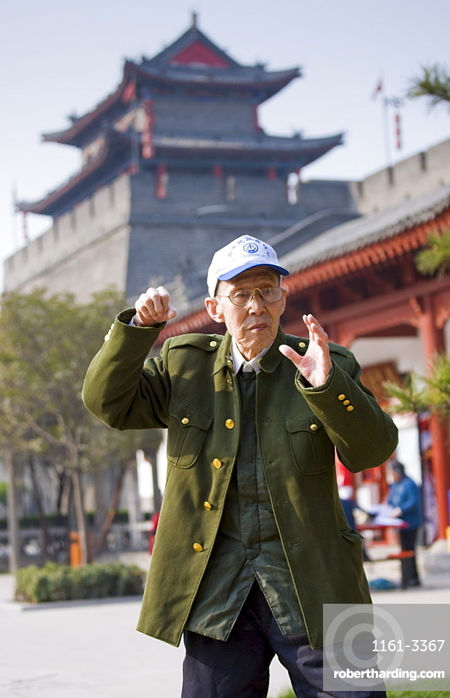 Man practises Tai chi as part of his morning exercise in the park by the City Wall of Xian, China