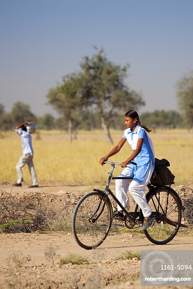 Young Indian girl in school uniform riding bicycle to her school near Rohet in Rajasthan, Northern India