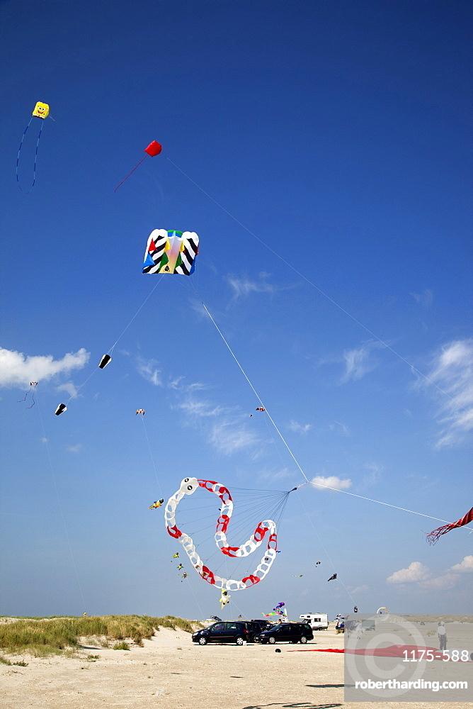 Multi-coloured flags in sky on kite festival at Fano beach, Denmark