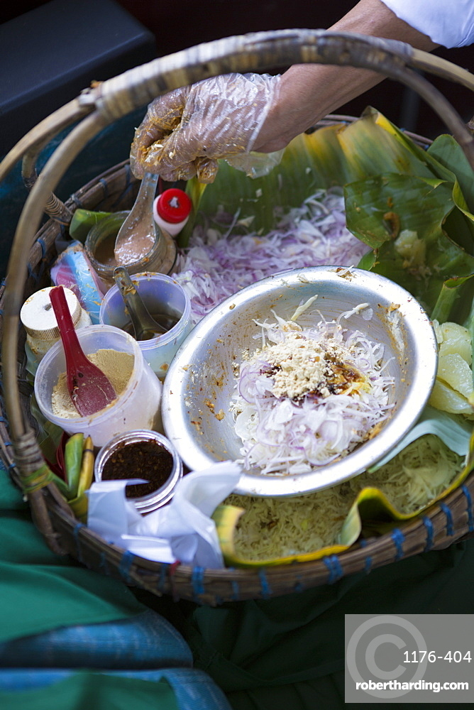 A snack seller offering stuffed banana leaf, onion and nut snacks on a train to Mandalay, Myanmar (Burma), Southeast Asia