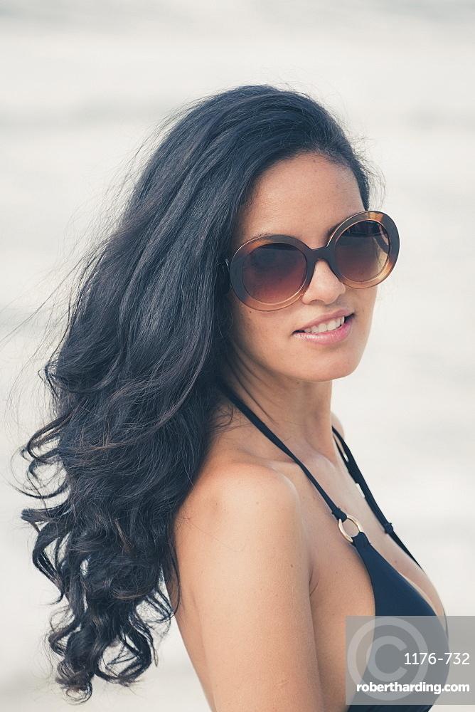 Young Brazilian (Latin American) (Latina) woman on the beach in a bikini and sunglasses, Rio de Janeiro, Brazil, South America