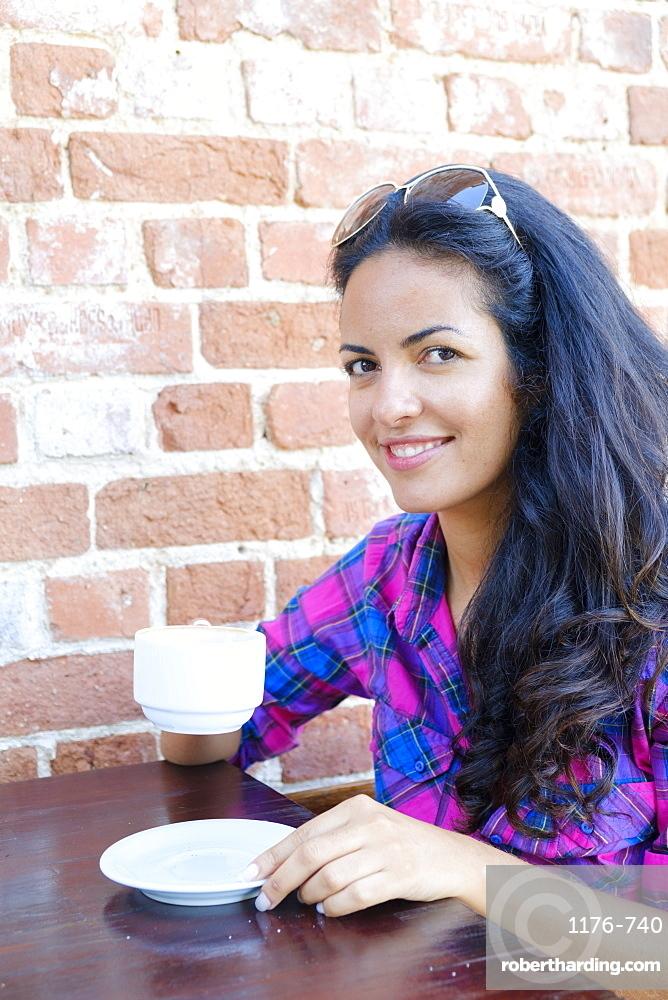 Young Brazilian (Latin American) (Latina) woman, 20 to 29 years old drinking coffee in a Rio cafe, Rio de Janeiro, Brazil, South America
