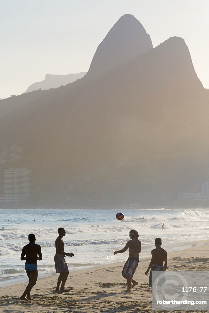 Locals playing football on Ipanema beach with the Morro dos Dois Irmaos (Two Brothers) mountains behind, Rio de Janeiro, Brazil, South America