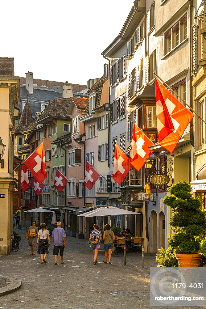 Tourists look at the Swiss Flags hanging from buildings in Lindenhof, Zurich, Switzerland