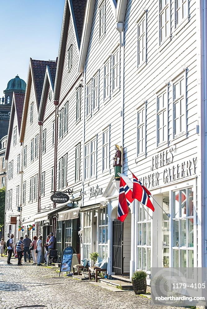 Norwegian flags hanging from white wood buildings and shops, Bryggen, Bergen, Hordaland County, Western Fjords region, Norway, Scandinavia, Europe