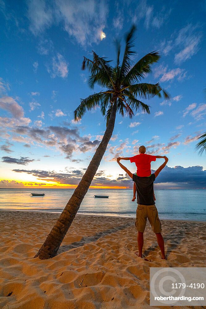 Rear view of cheerful father holding his son on neck standing on tropical sand beach, Le Morne Brabant, Mauritius, Indian Ocean, Africa