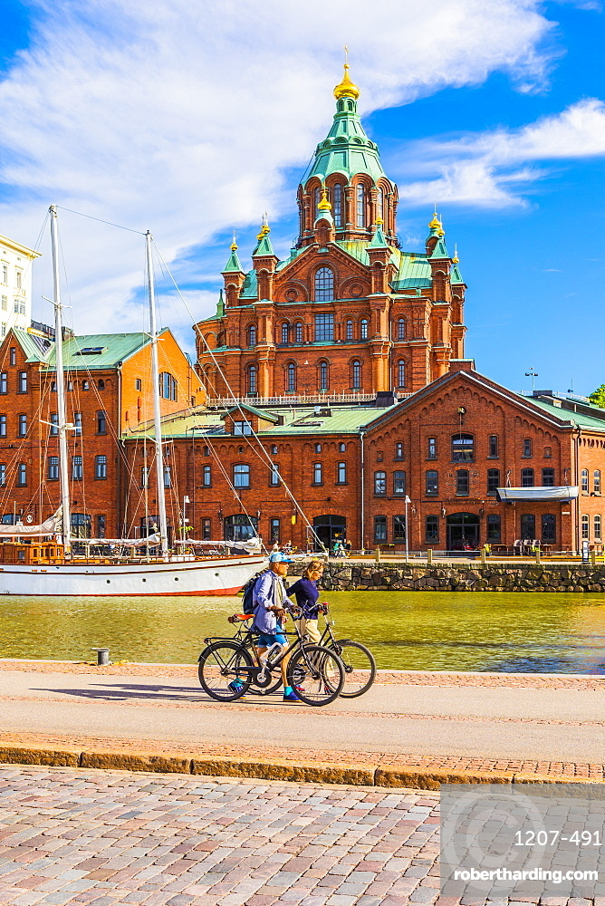 Uspenski Cathedral and cyclists by harbor in Helsinki, Finland, Europe