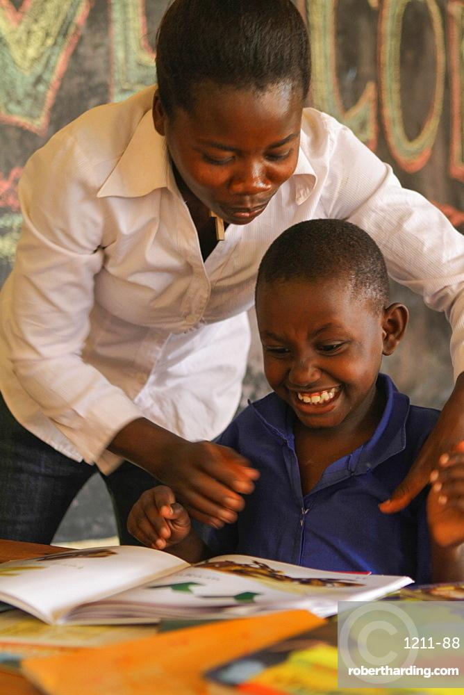 Isingizwe Alice, 8 years old, who is dumb and her teacher Musabyemariya Alphonsine from Ngwino Nawe, teaching Alice how to read a book using signs, Rwanda, Africa
