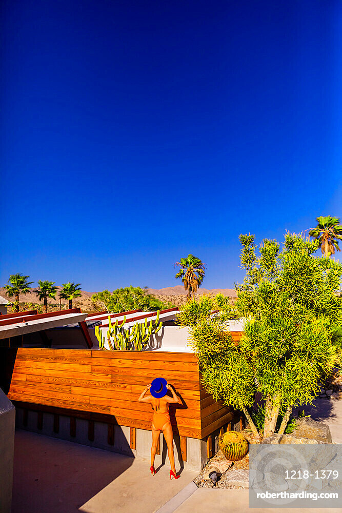 View of beautiful desert home and woman getting a tan.