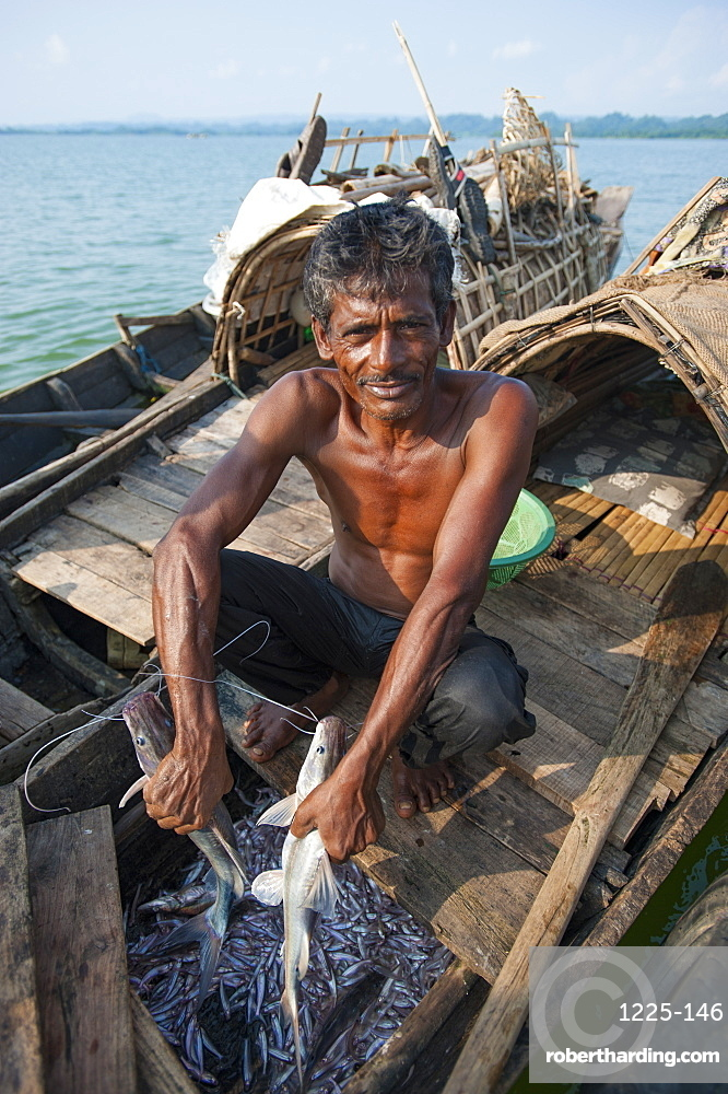 A fisherman holds a fresh catch on Kaptai Lake in the Chittagong Hill Tracts, Bangladesh, Asia