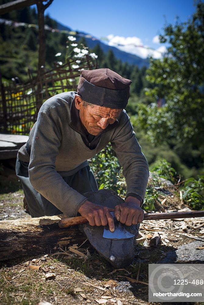 A Tamang man in the Tamang Heritage region close to Langtang sharpens an axe in the traditional way, Langtang Region, Himalayas, Nepal, Asia