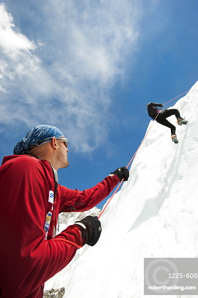 A climber makes her way down an ice wall in preparation for climbing Everest, Khumbu Region, Nepal, Asia