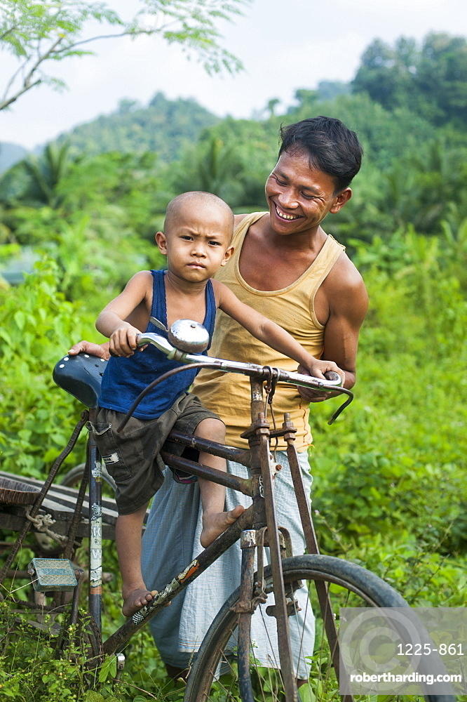 A man balances his little boy on his bicycle, Chittagong Hill Tracts, Bangladesh, Asia