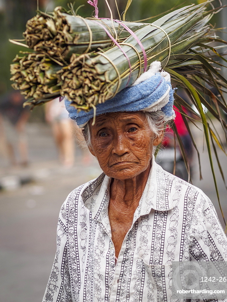 Old woman carries palm leaves on her head, Ubud, Bali, Indonesia, Southeast Asia, Asia