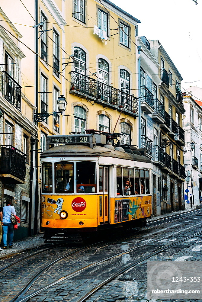 Traditional yellow electric tram in a narrow street in Alfama, Lisbon, Portugal, Europe