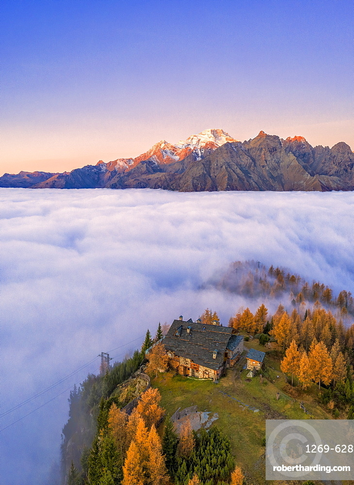 Fog covers the Valmalenco (Val Malenco) with Mount Disgrazia illuminated by sunrise and the Motta hut, Valtellina, Lombardy, Italy, Europe