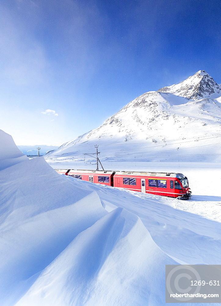 Bernina Express transit along Lago Bianco during winter blizzard, Bernina Pass, Engadine, Graubunden canton, Switzerland, Europe