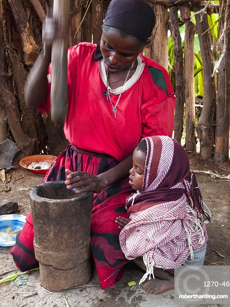 A woman uses a traditional wooden pestle and mortar to grind freshly roasted coffee beans, Ethiopia, Africa