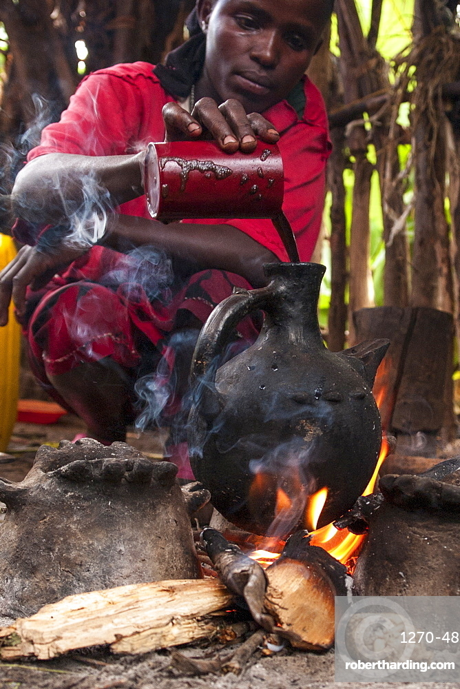 A woman pours into a traditional Ethiopian coffee pot on an open fire, Ethiopia, Africa