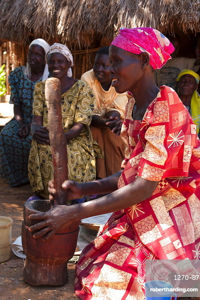 A woman pounding millet using a traditional wooden pestle and mortar at her home compound, Uganda, Africa