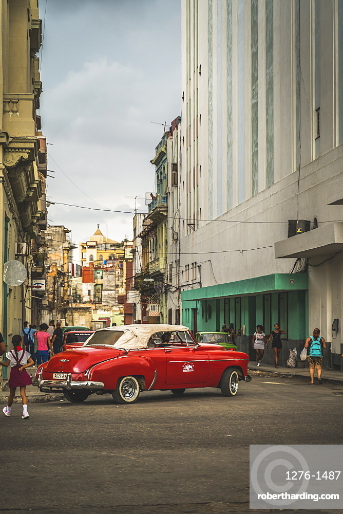Red vintage car turning in streets of La Habana (Havana), Cuba, West Indies, Caribbean, Central America