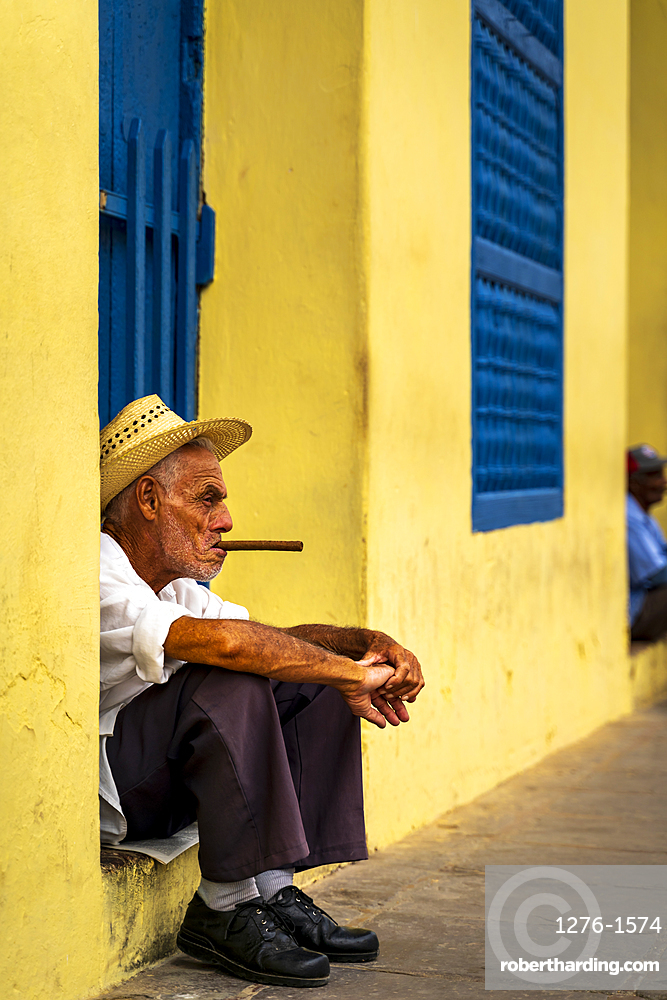 An elderly Cuban sitting on a doorstep, smoking a cigar, Trinidad, Sancti Spiritus Province, Cuba, West Indies, Caribbean, Central America