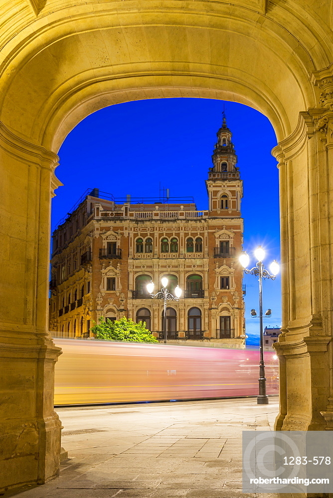 Light trails of the tram passing historical building at Plaza Nueva at dusk, Seville, Andalusia, Spain, Europe