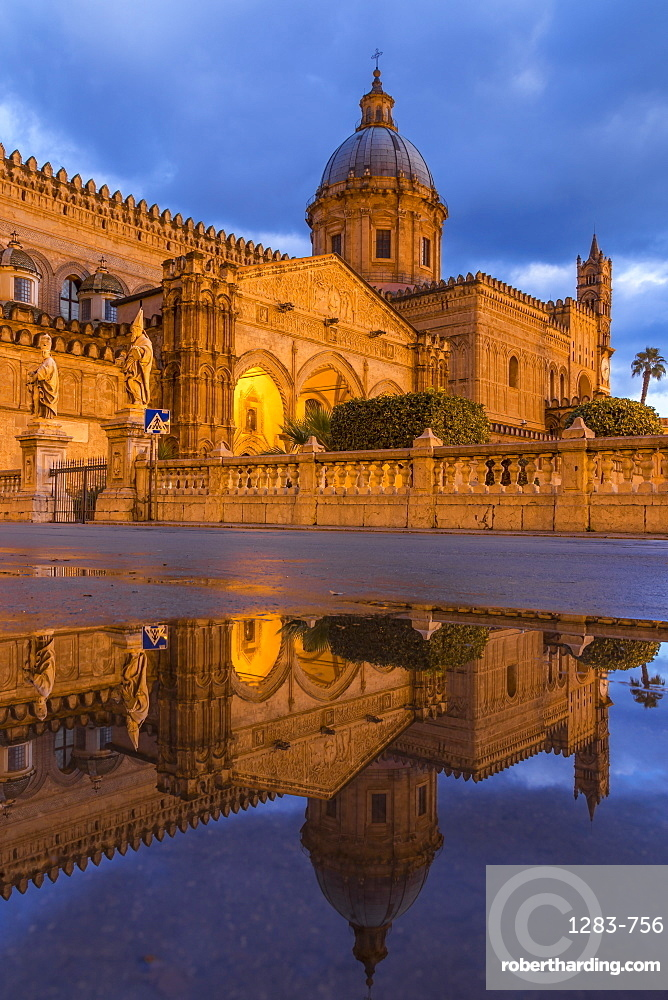 The illuminated Palermo Cathedral (UNESCO World Heritage Site) reflected in a puddle, Palermo, Sicily, Italy, Europe