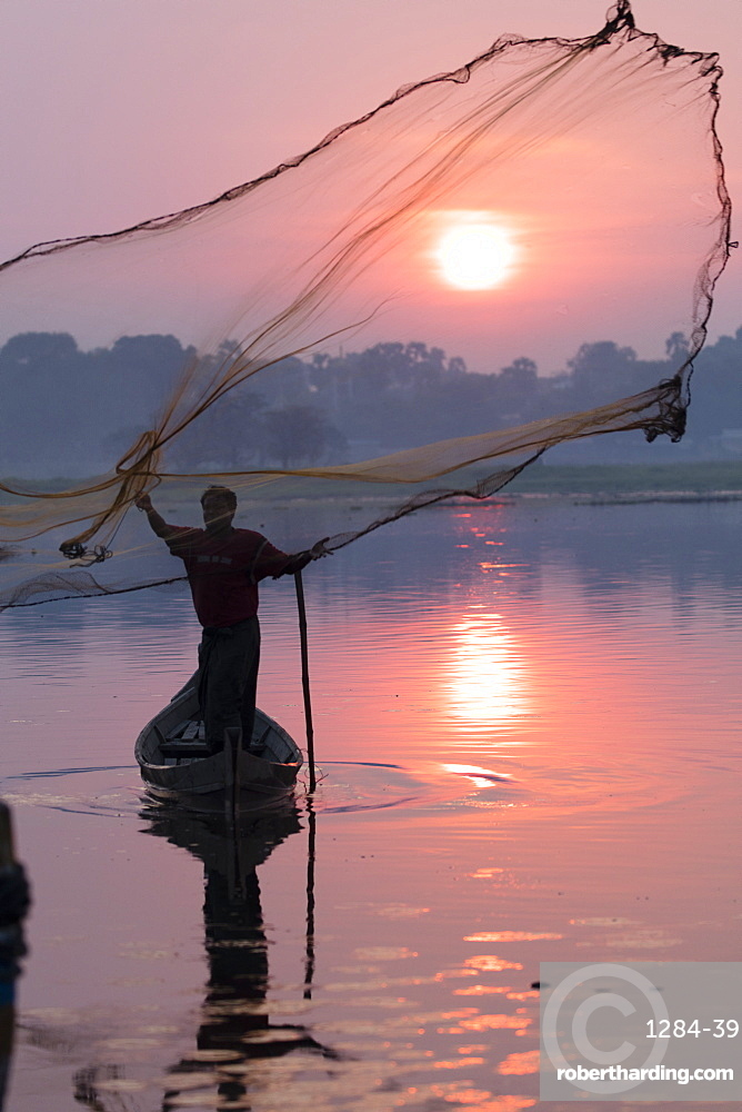 Fisherman casts his net at sunrise on Lake Taungthaman near U Bein Bridge, Myanmar (Burma), Asia