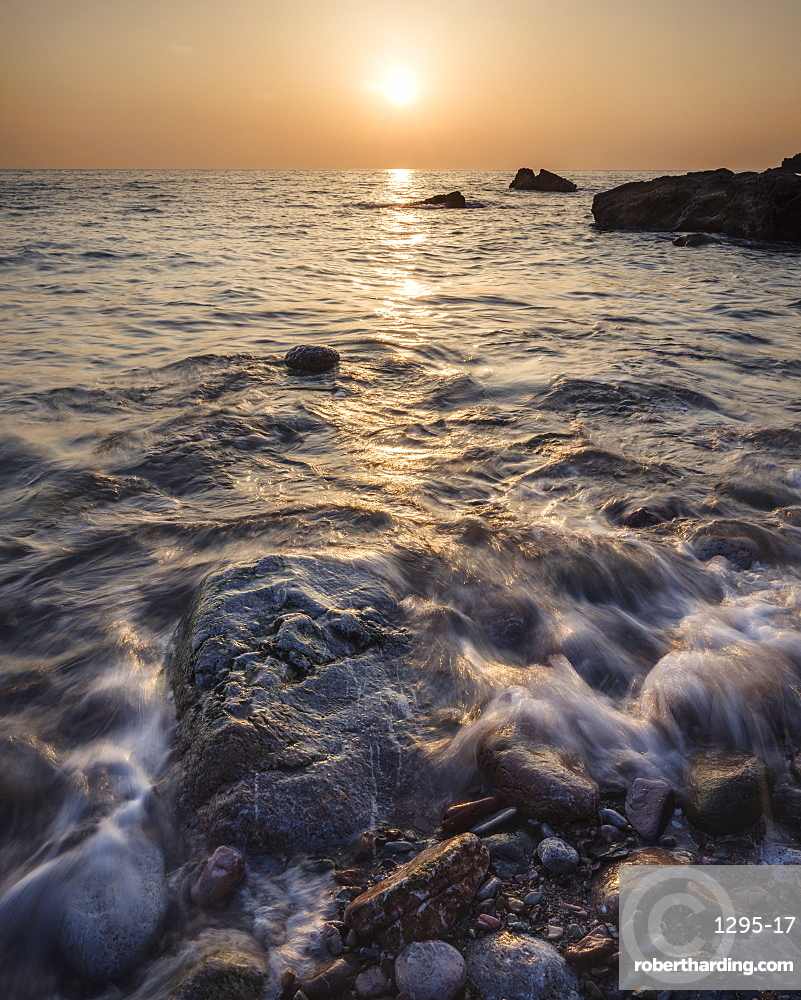 A colourful sunrise over Torbay with warm light glinting off the wave and wet rocks, Anstey's Cove, Torquay, Devon, England, United Kingdom, Europe
