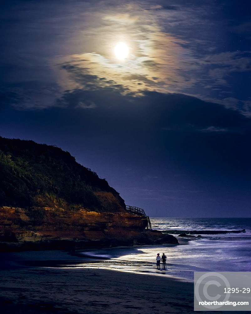 Two ladies paddle whilst watching the full Blood Moon, shortly after an eclipse at Orcombe Point, Exmouth, Devon, England, United Kingdom, Europe