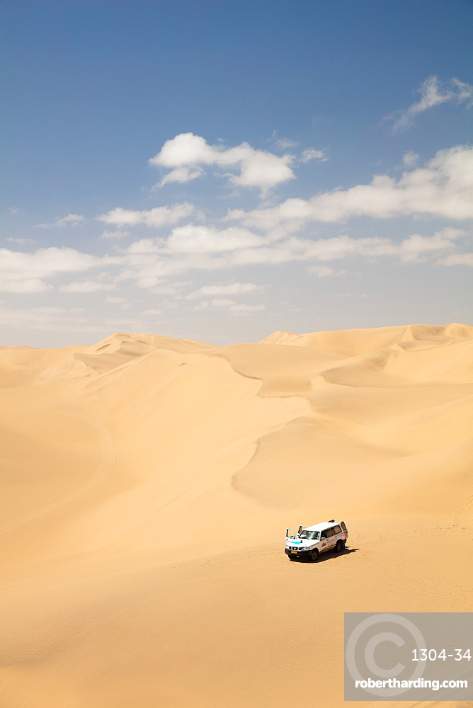 A car pictured within the Sandwich Harbour dunes, Skeleton Coast at midday, Namibia, Africa